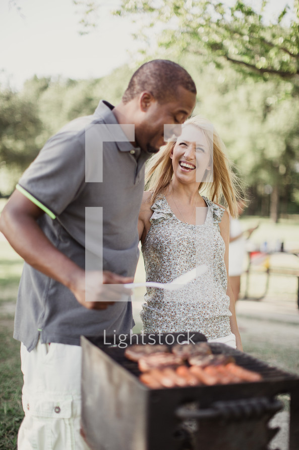A man and woman laughing together while cooking on an outside grill.