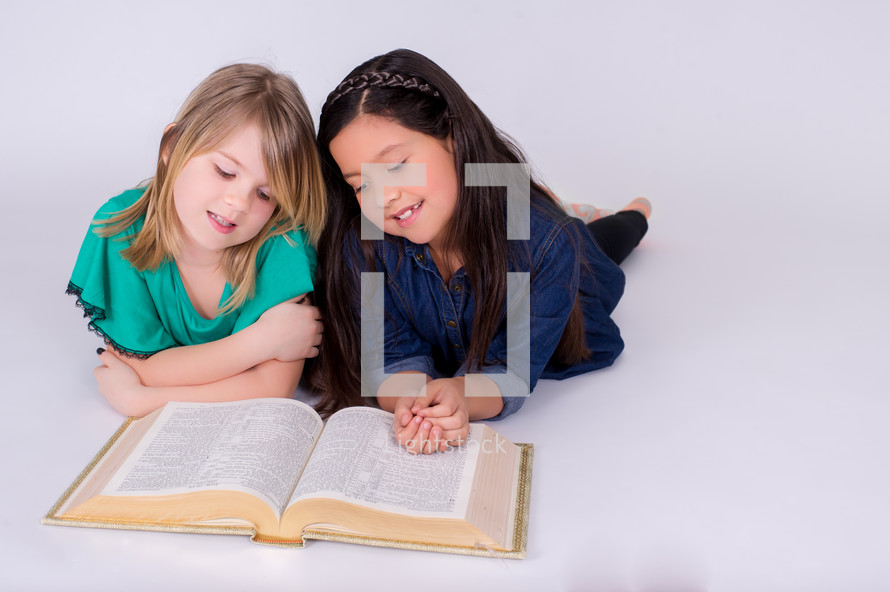 Girls reading the Bible while sitting on the floor.