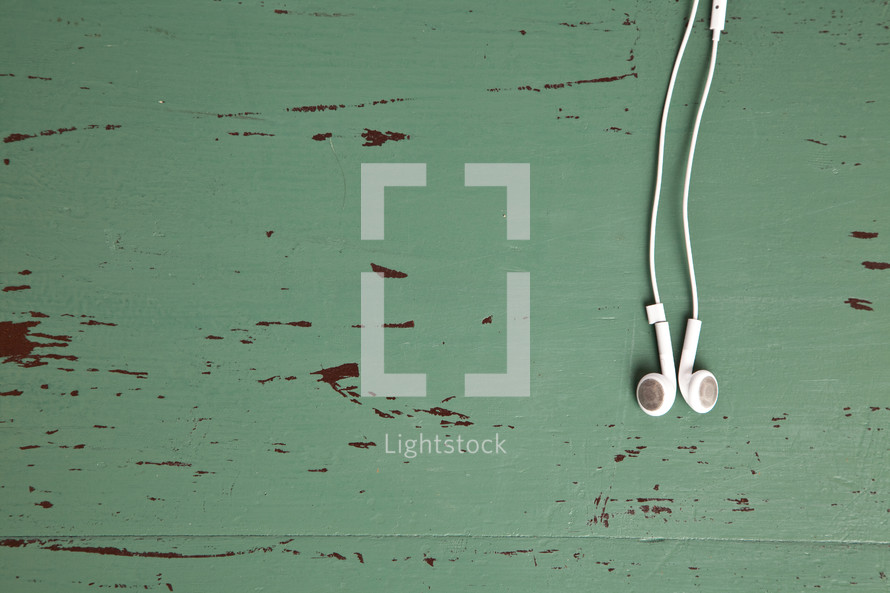 earbuds laying on a an old green table.