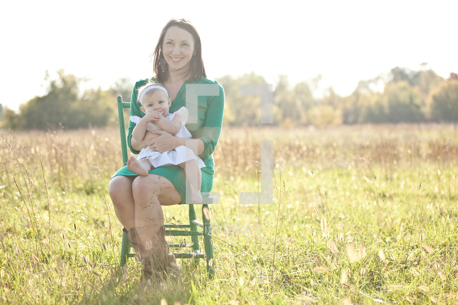mother sitting in a green chair outdoors holding her infant daughter