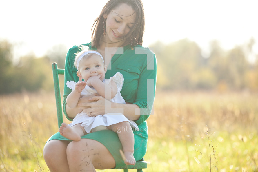 Mother holding toddler daughter while sitting in a chair in a field.