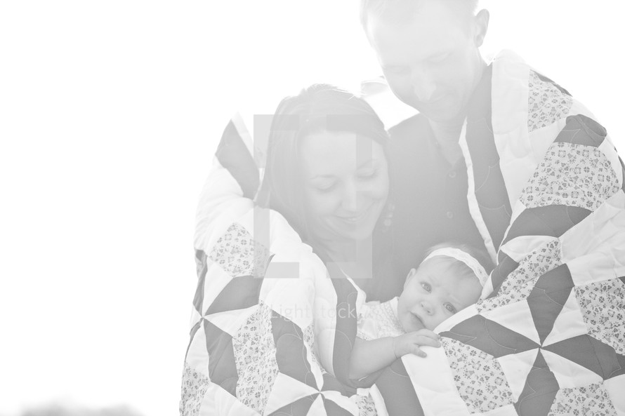 Couple holding infant daughter while all wrapped in a quilt.