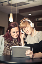 two women listening to music through headphones from an iPad