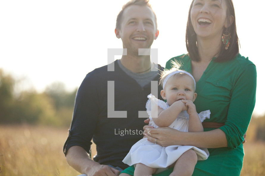 Mom and dad holding infant daughter while standing in a field.