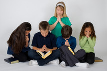 Children praying together over the Bible.