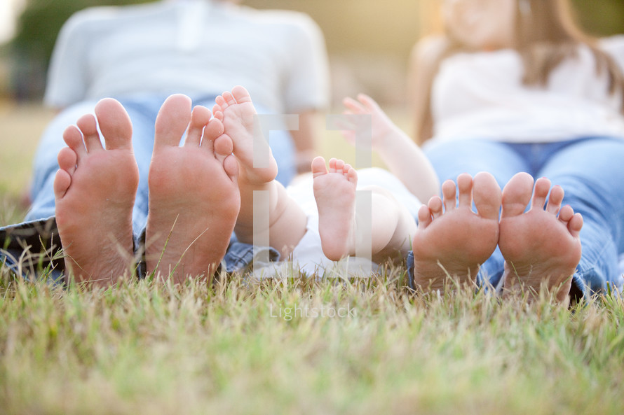 feet of a mother, father, and baby