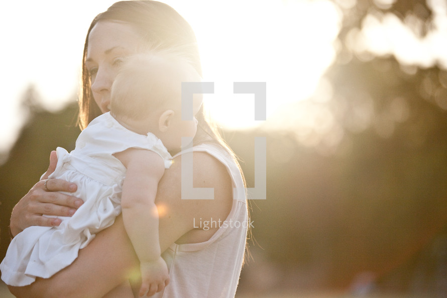 Mother holding infant in the sunlight.