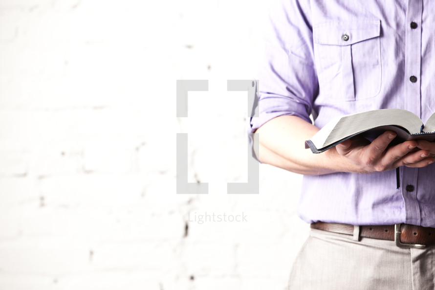 man holding an open Bible
