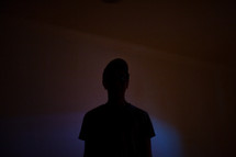 silhouette of a young man in a dark room
