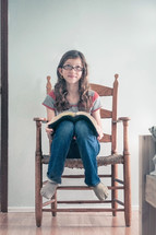 A girl sitting in a bedroom chair with an open bible, thinking.
