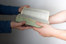 Hands passing a Bible.