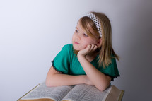 Girl thinking over the Bible.