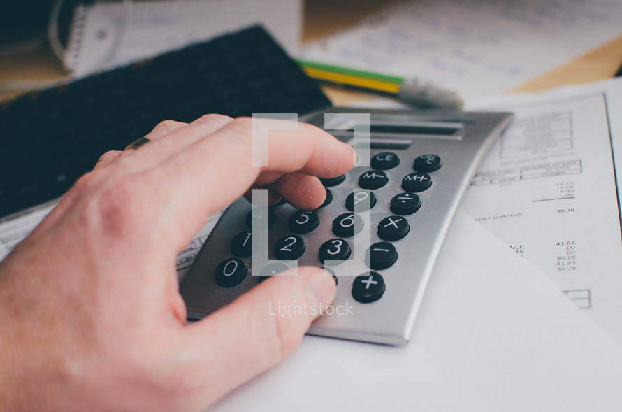 A man's hand punches in numbers on a calculator sitting atop of bills on a desk