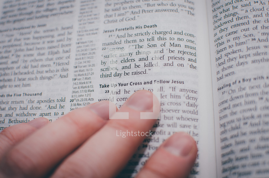 An open bible with fingers pointing to the passage entitled 'Take up your cross and follow Jesus'.