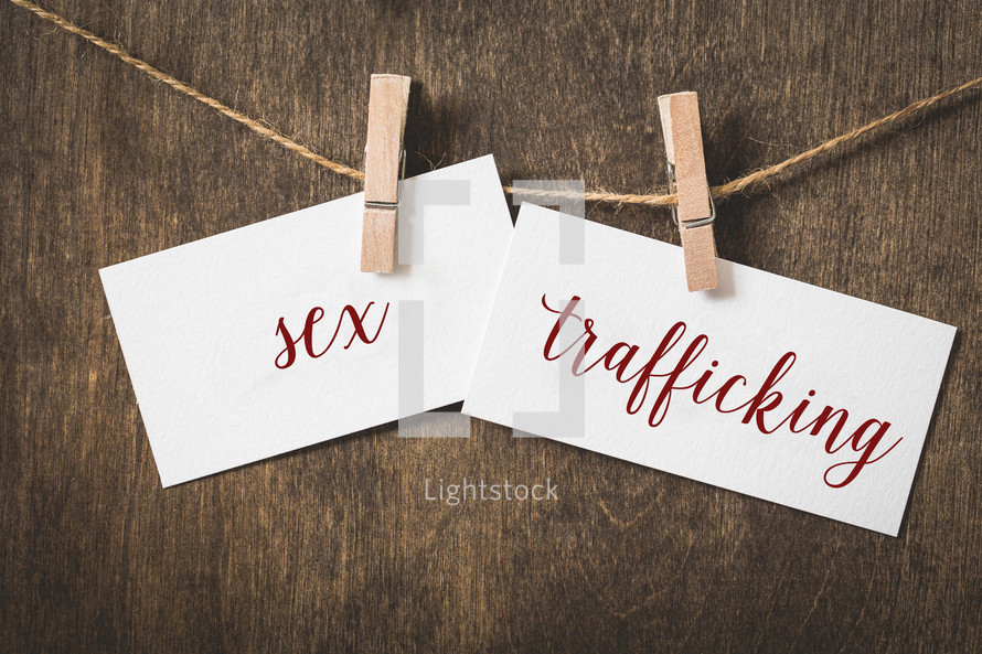 words sex trafficking on card stock hanging on twine by a clothespin