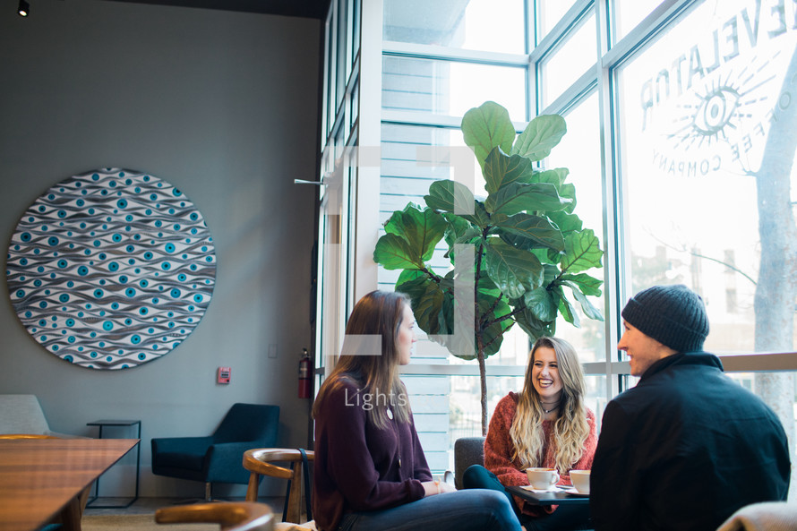 small group of young adults sitting in a window seat talking over coffee