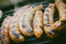 sausages cooking on a bbq grill