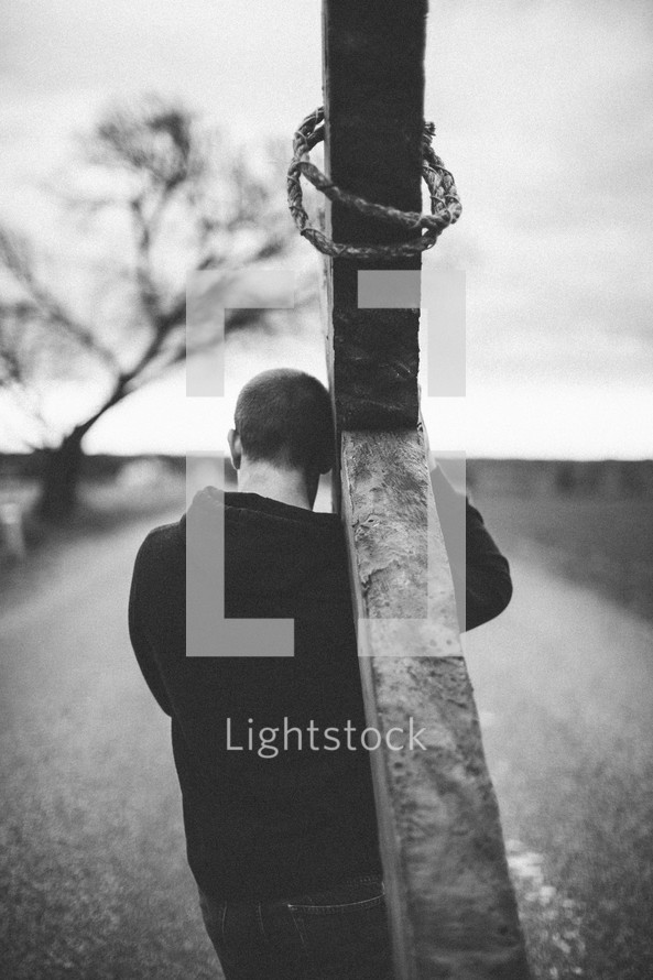 man carrying a large cross along the highway - re-enacting Christ's walk, bearing the cross