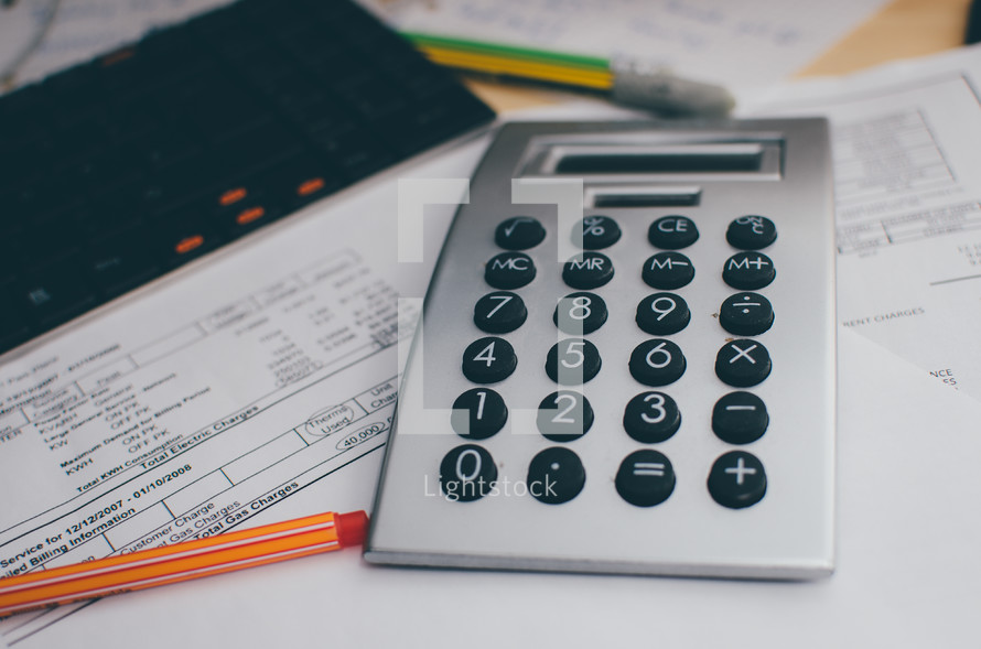 A calculator and red pen sit on top of a desk with a keyboard and bills