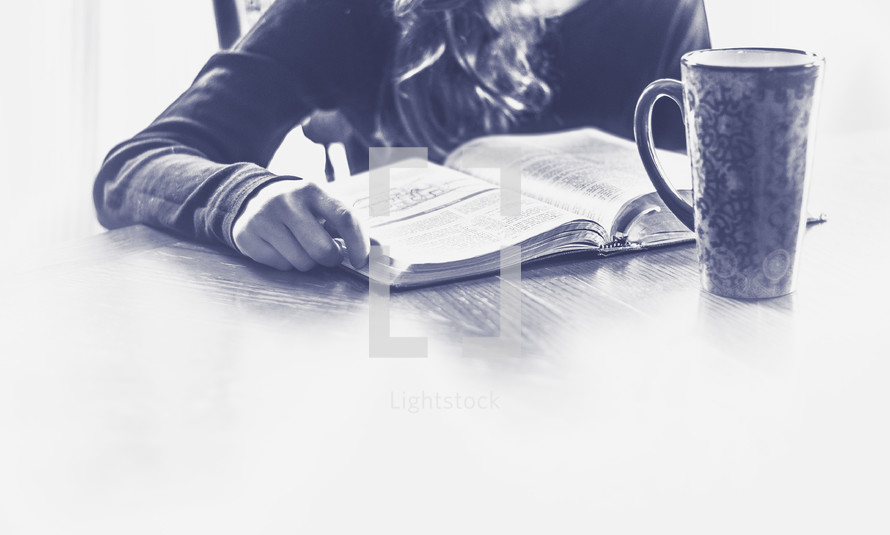 girl reading a Bible at the kitchen table
