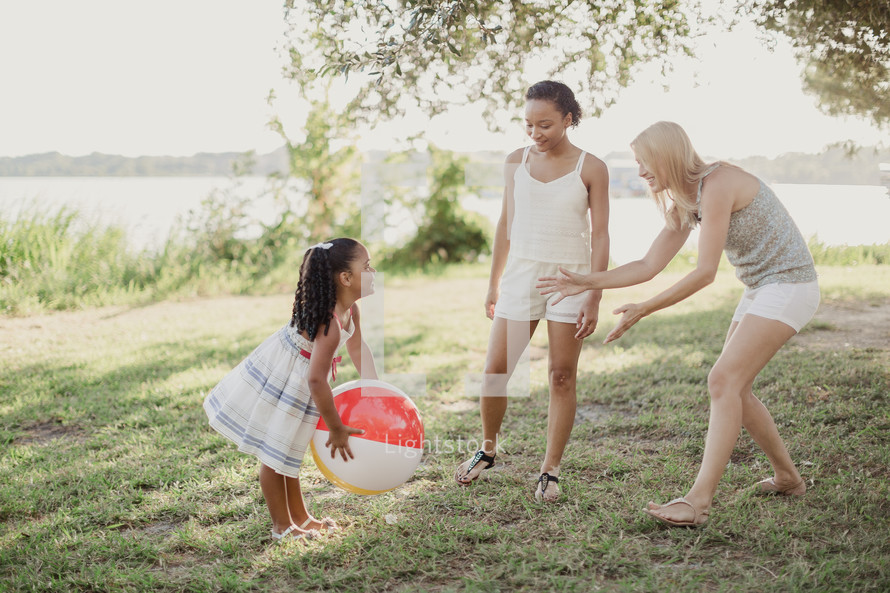 Two young women and a little girl playing catch with a beach ball.