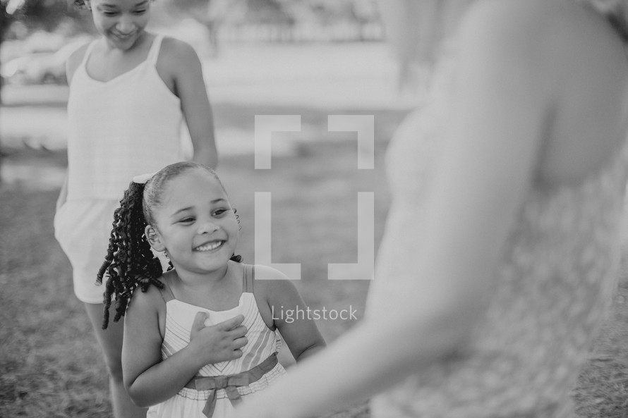 Two women and a little girl laughing together outdoors.