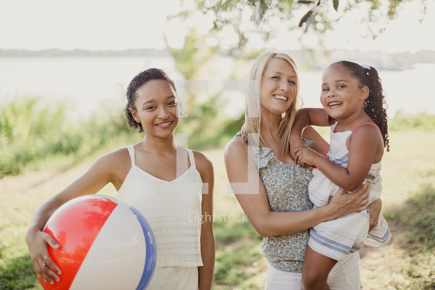 Two young women and a little girl standing together and smiling.