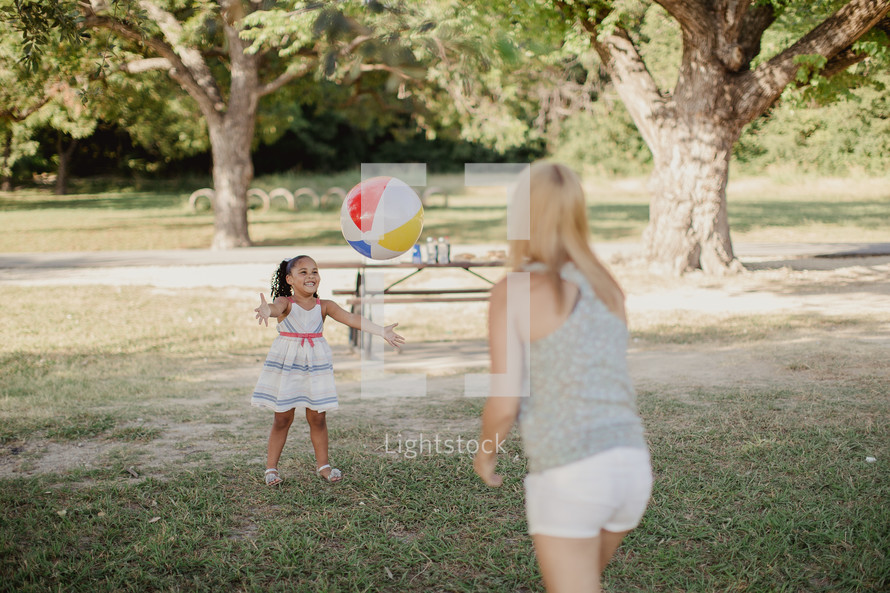 A young woman and little girl playing catch with a beach ball.