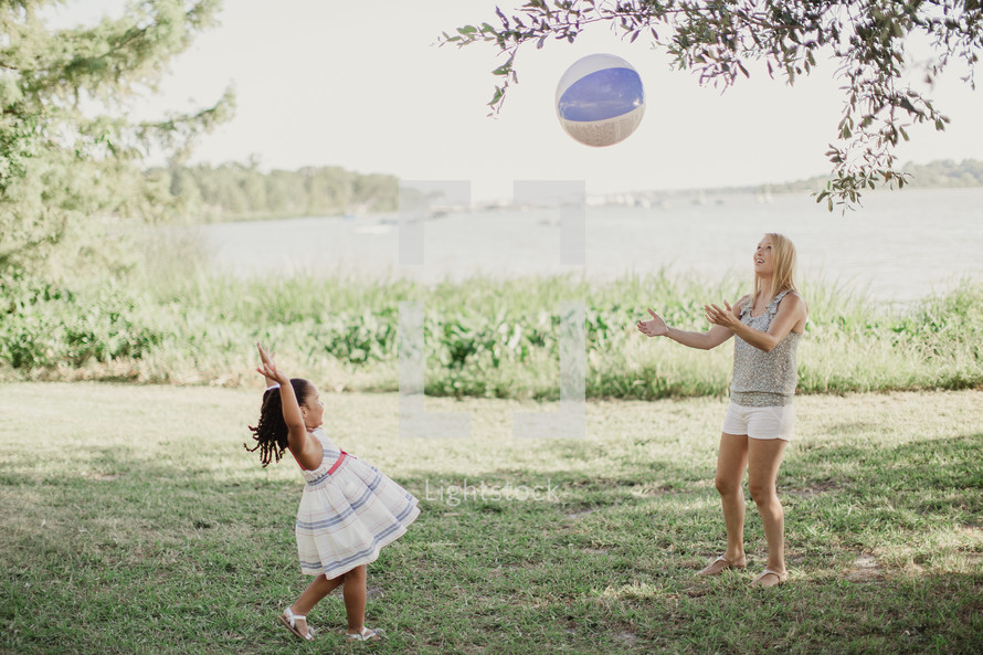 A little girl throwing a beach ball to a young woman.