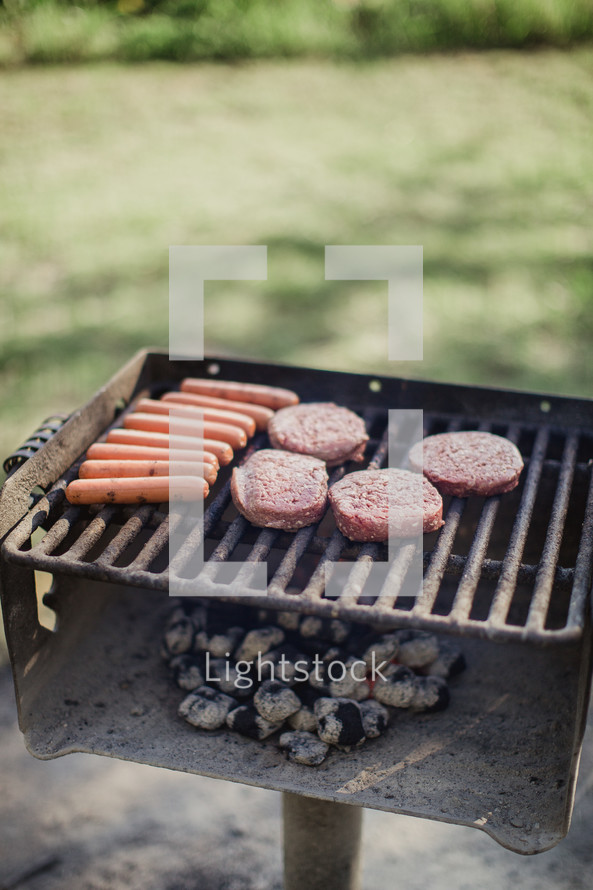 Hot dogs and hamburgers cooking over hot coals on an outside grill.