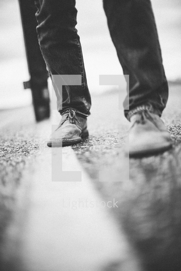 a man's feet on the pavement as he carries a large cross re-enacting Christ's walk, bearing the cross