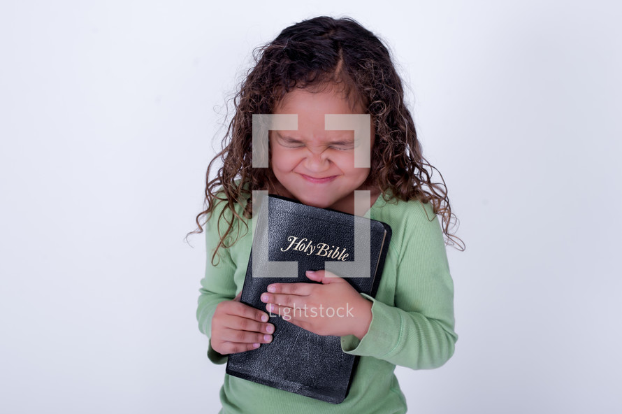Girl squeezing a closed Bible.