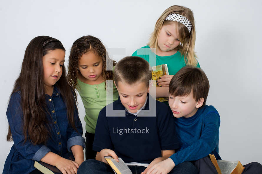 Children reading the Bible together.