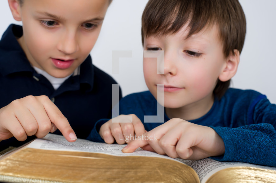 Boys reading the Bible together.