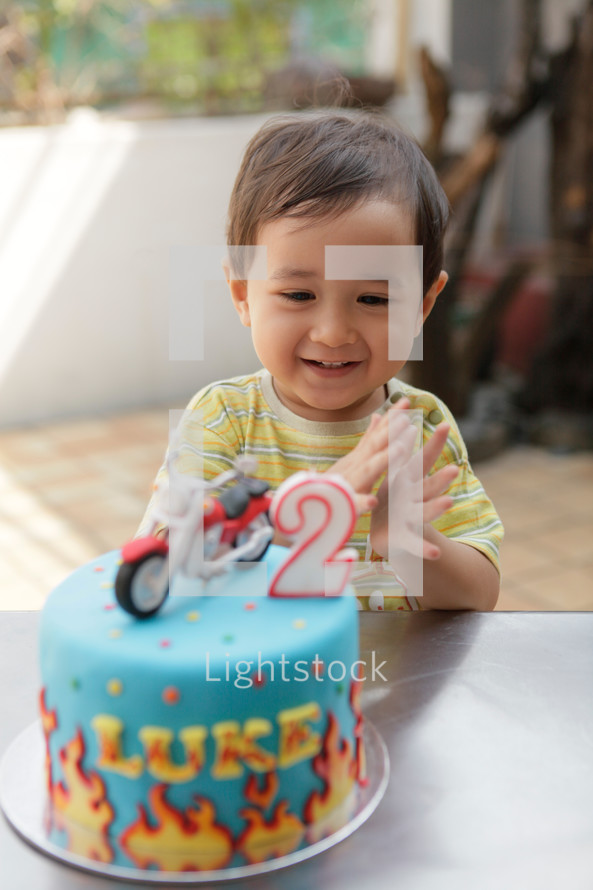 Happy Asian toddler boy clapping his hands after blowing out the candle on his cake. Shot outdoors.
