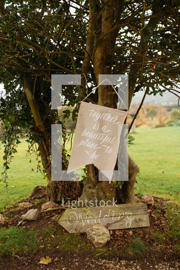 together is a beautiful place to be sign hanging on a tree for a wedding