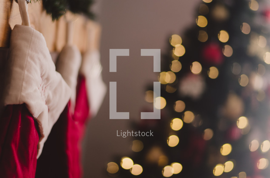 lights on a Christmas tree and stocking hanging on a mantle