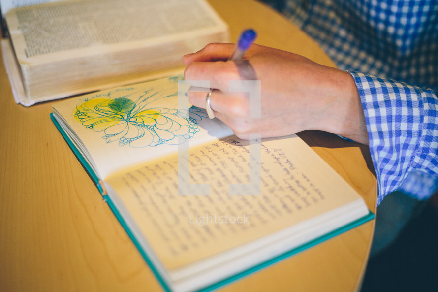 Woman's hand drawing in a notebook with an open bible on the table
