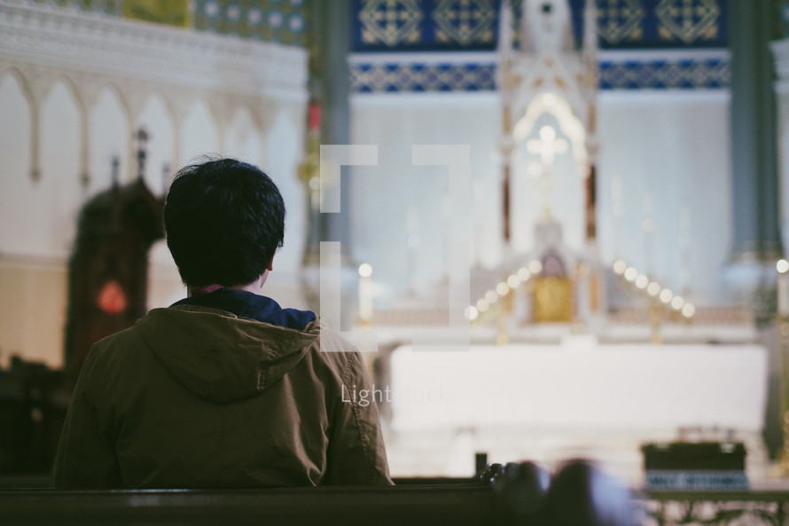 A young man praying in a large Catholic church