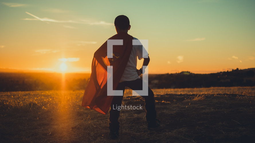 Boy facing the sun wearing a superman cape.