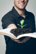 man holding a Bible with soil and a plant growing in its pages