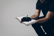 man holding a Bible with soil and a plant growing from its pages