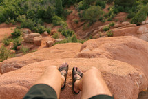 feet at the edge of a red rock cliff