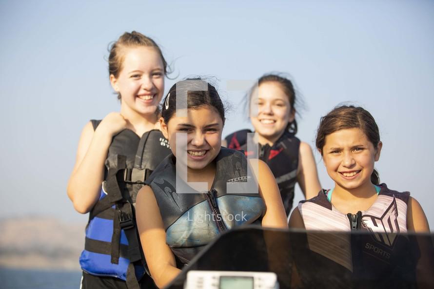 kids on a boat in life vests