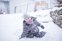 a boy child playing in snow