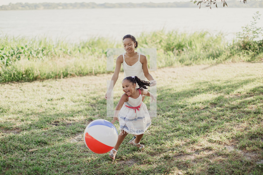 A young woman and little girl playing outdoors with a beach ball.