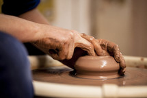 hands on clay on a potter's wheel