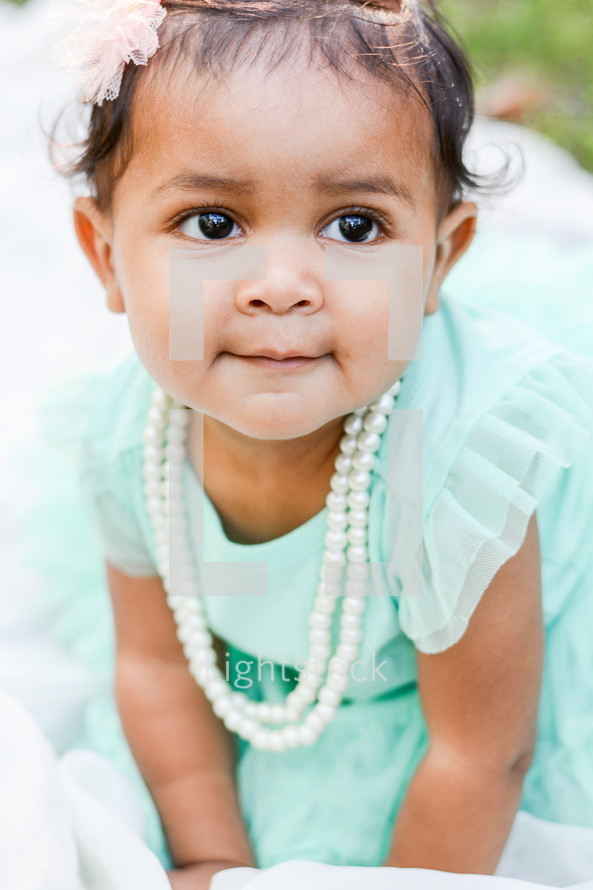 face of an infant girl in a mint green dress with pearls