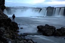 person watching a waterfall in Iceland