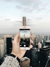 man taking a picture of a skyscraper with his cellphone